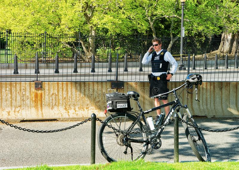 Policeman and his bicycle in street of Washington DC. Washington D.C., USA - May 2, 2015: Policeman and his bicycle in the street of Washington D.C. performing royalty free stock image