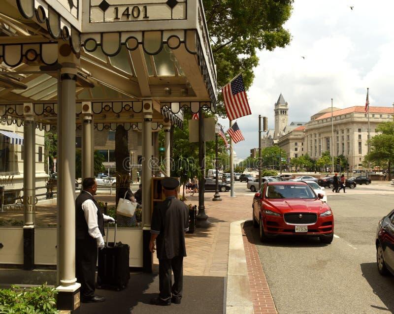 Washington DC - Juni 02, 2018: Hotellportvakten och den röda taxien n royaltyfri fotografi