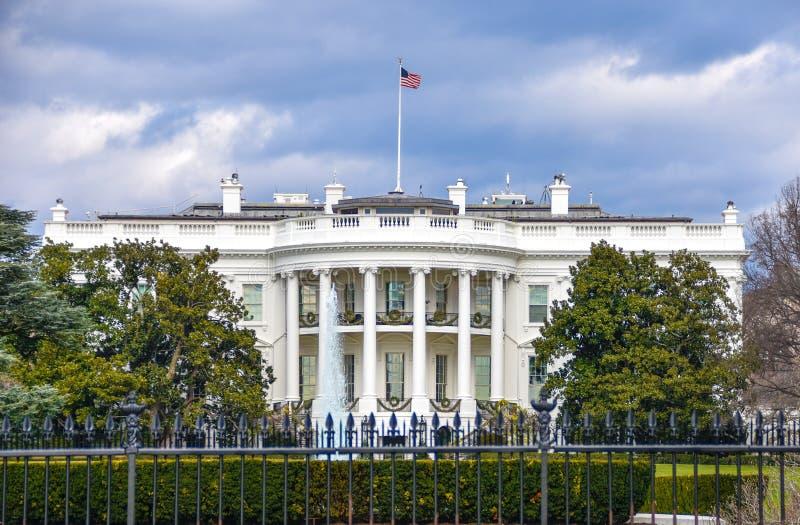 Washington DC, los E Opinión de la Casa Blanca sobre fondo nublado del día y bandera americana foto de archivo