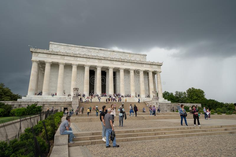Washington DC - May 9, 2019: Crowds of tourists visit the Lincoln Memorial monument, as a severe thunderstorm rolls in royalty free stock images