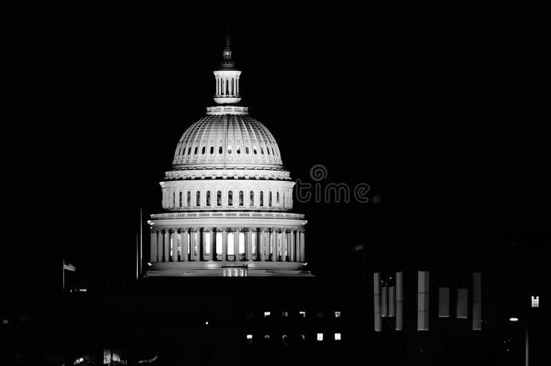 Washington, gelijkstroom-District Colombia/de V.S. - 08 20 2018: De het Capitoolbouw van de V.S. bij nacht met twee vlaggen die h stock foto's