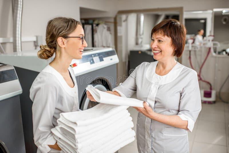 Washwoman senior con il giovane assistente nella lavanderia fotografie stock