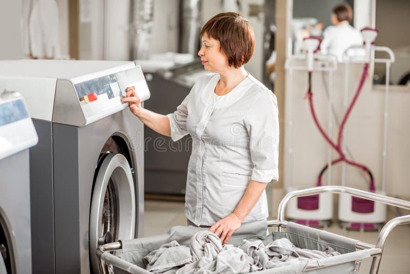 Washwoman senior nella lavanderia immagine stock