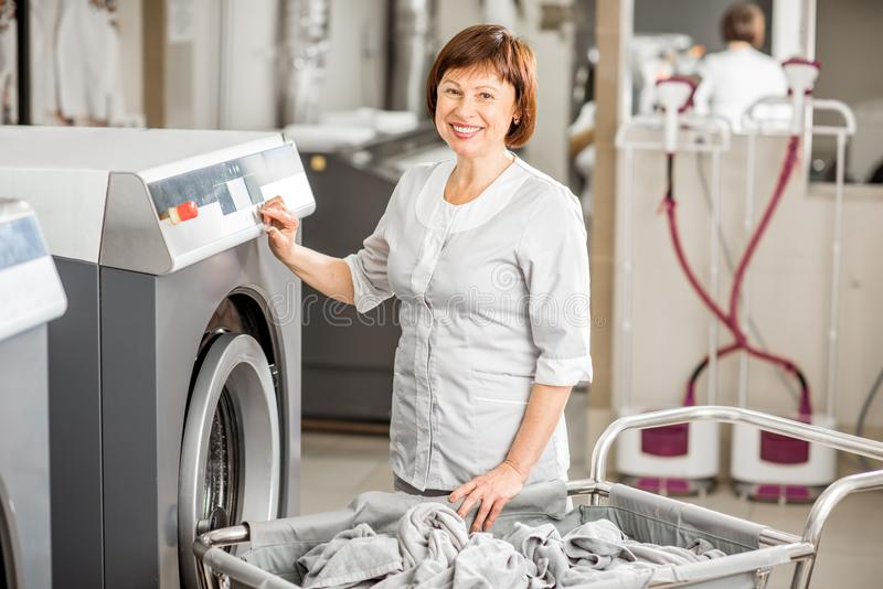 Washwoman senior nella lavanderia fotografia stock