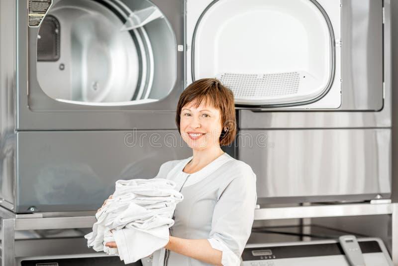 Washwoman senior nella lavanderia fotografie stock