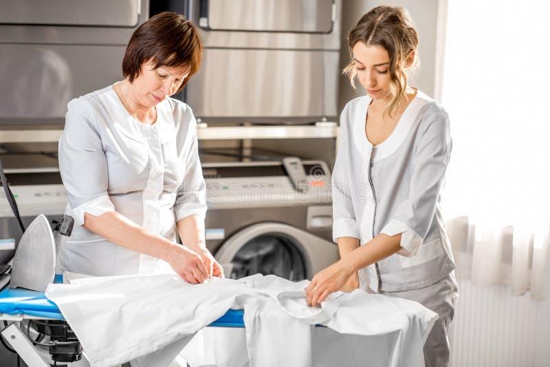 Washwoman senior nella lavanderia immagini stock libere da diritti