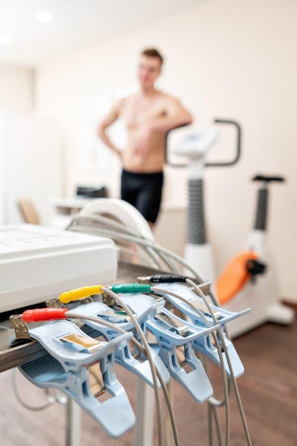 Wasknijpers van de ECG-machine in de voorgrond De atleet doet een hartspanningstest en VO2 in een medische studie stock afbeeldingen
