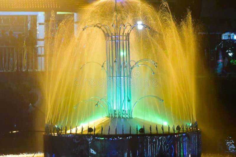 Wasser-Brunnen mit gelblicher und grüner Beleuchtungs-Hintergrund-Fotografie stockfotos