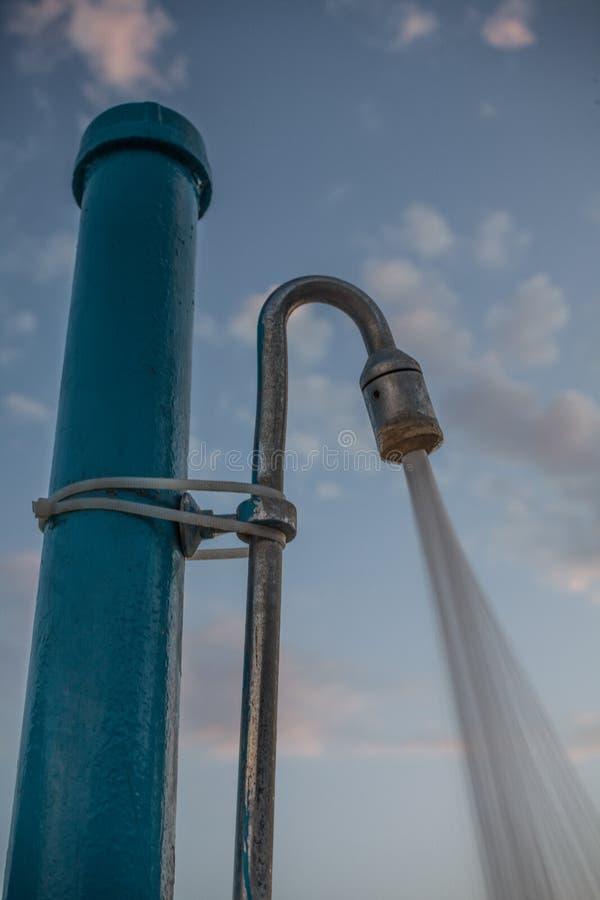 Wasser, das aus Duschkopf gießt Allgemeine Dusche für Schwimmen im Freien unter dem blauen bewölkten Himmel Nahaufnahme-Winkel-Sc stockfotos