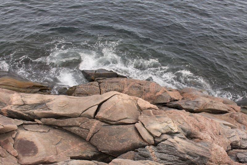 Wasser, das oben auf Felsen zusammenstößt stockfotografie