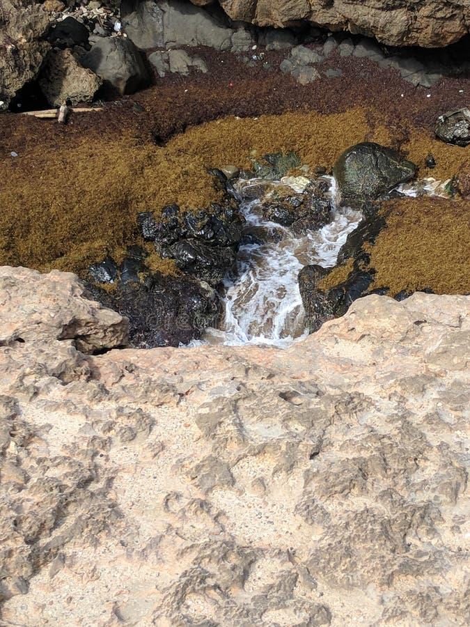 Wasser, das unten aus einem großen Tidepool heraus fließt stockfotos