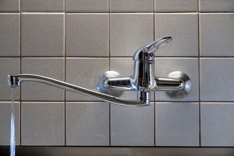 Wasser, das vom Hahn mit einer schädigenden Dichtung leckt Ein Hahn in der Küche lizenzfreies stockfoto