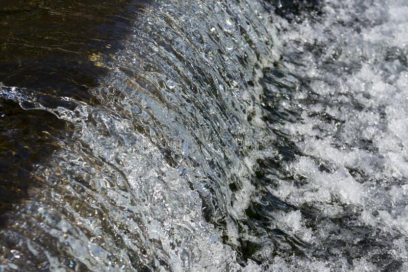 Wasser, das von der Verdammung fließt stockbild