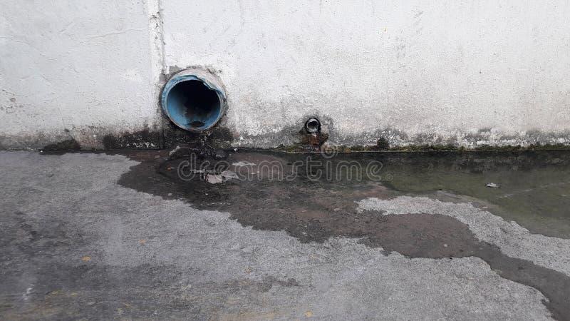 Wasser fließt Rohr auf Zementboden lizenzfreie stockfotos