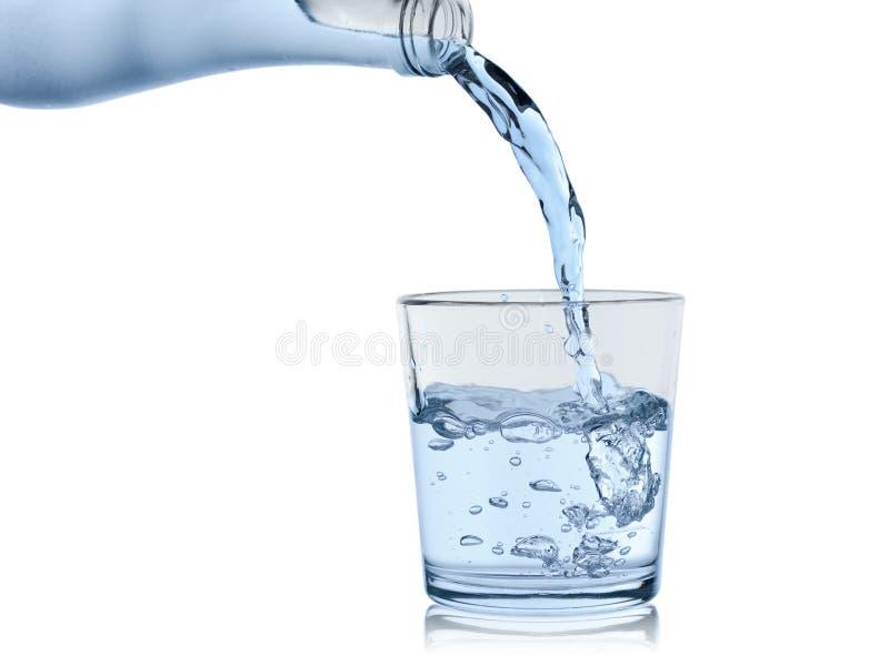 Wasser von der schwitzenden Flasche wird herein ein Glas/Glas gegossen, lokalisiert auf einem weißen Hintergrund lizenzfreie stockbilder