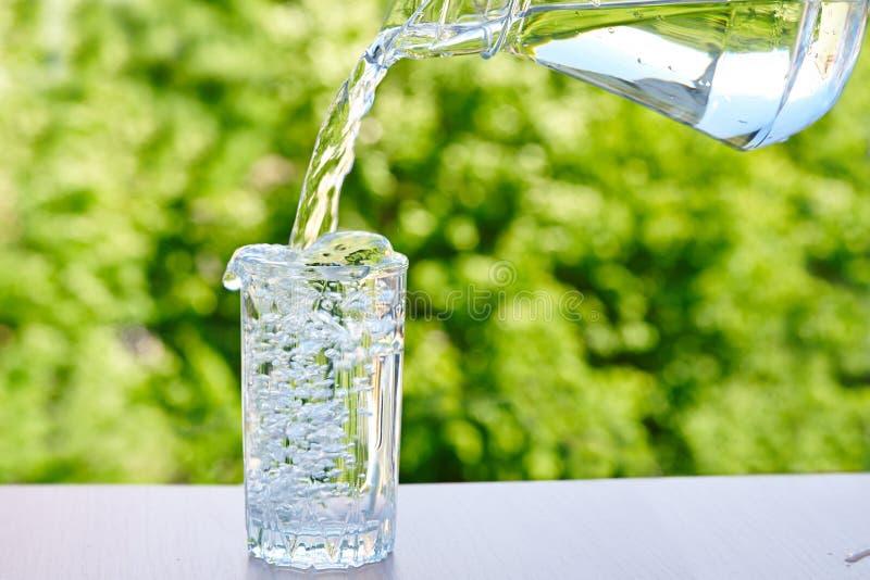 Wasser wird aus einem Krug in ein Glas gegossen lizenzfreie stockfotos