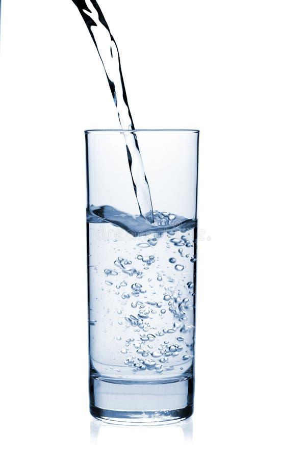 Wasser wird in ein Glas gegossen lizenzfreies stockbild