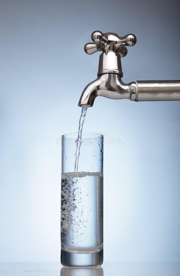 Wasser wird in ein Glas vom Hahn gegossen lizenzfreies stockbild