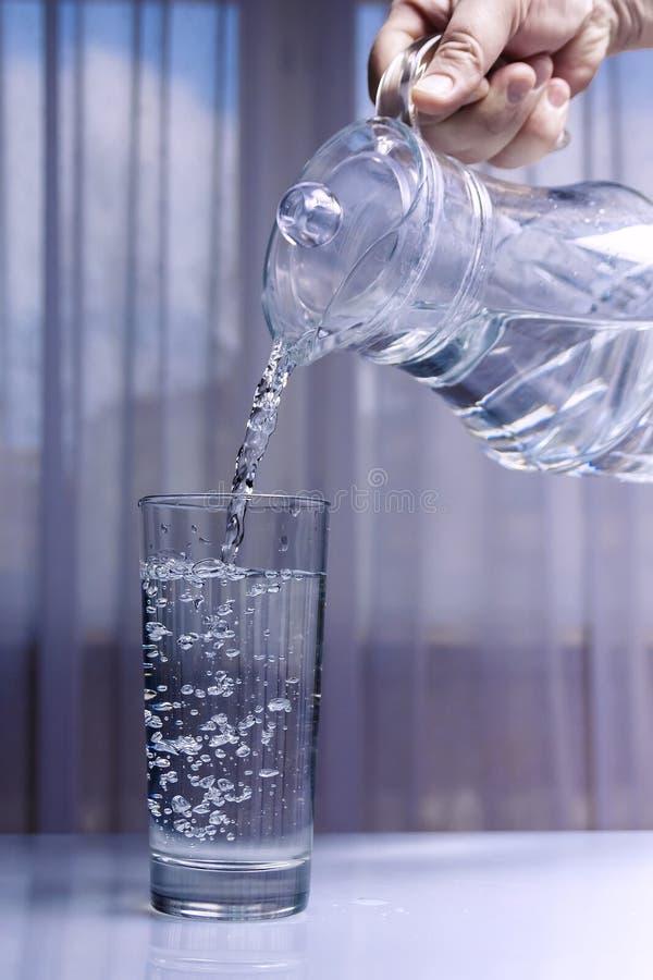 Wasser wird in ein Glas von einem Glasdekantiergefäß gegossen Heller einheitlicher Hintergrund des Hintergrundes nicht lizenzfreie stockbilder