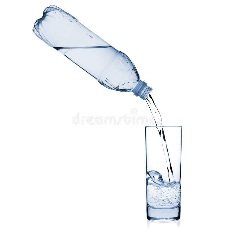 Wasser wird in ein Glas von einer Flasche gegossen lizenzfreie stockbilder