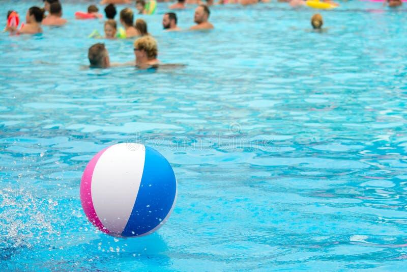 Wasserball, der in einen blauen Swimmingpool schwimmt Blaues Meer, Himmel u stockfoto