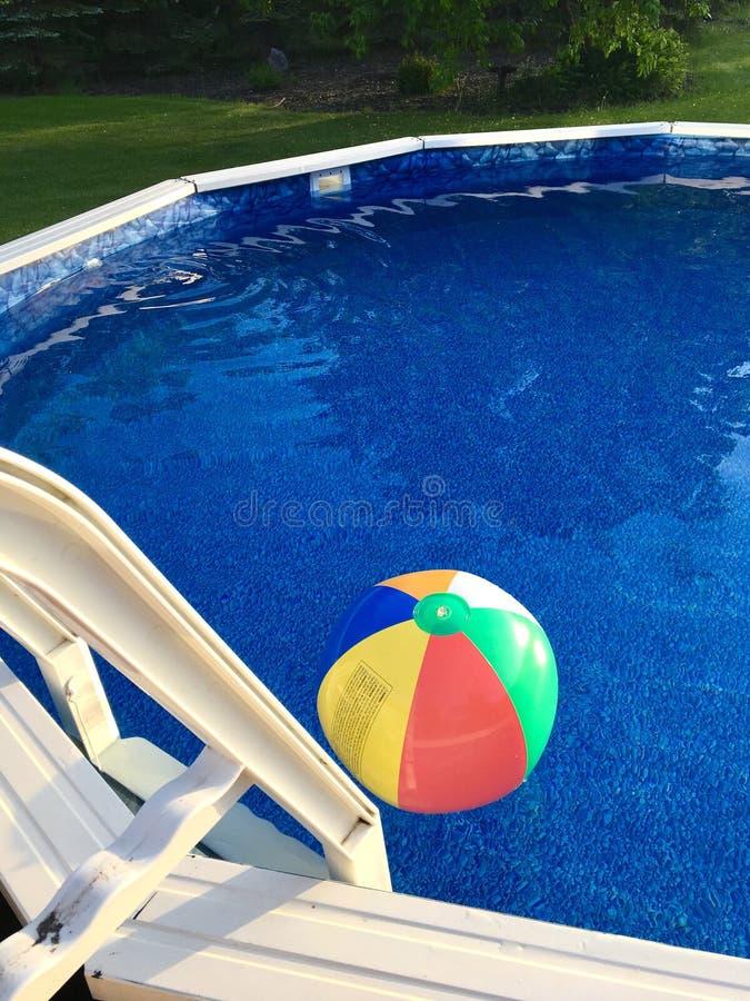 Wasserball schwimmt auf Oberfläche des oberirdischen Swimmingpools lizenzfreies stockfoto