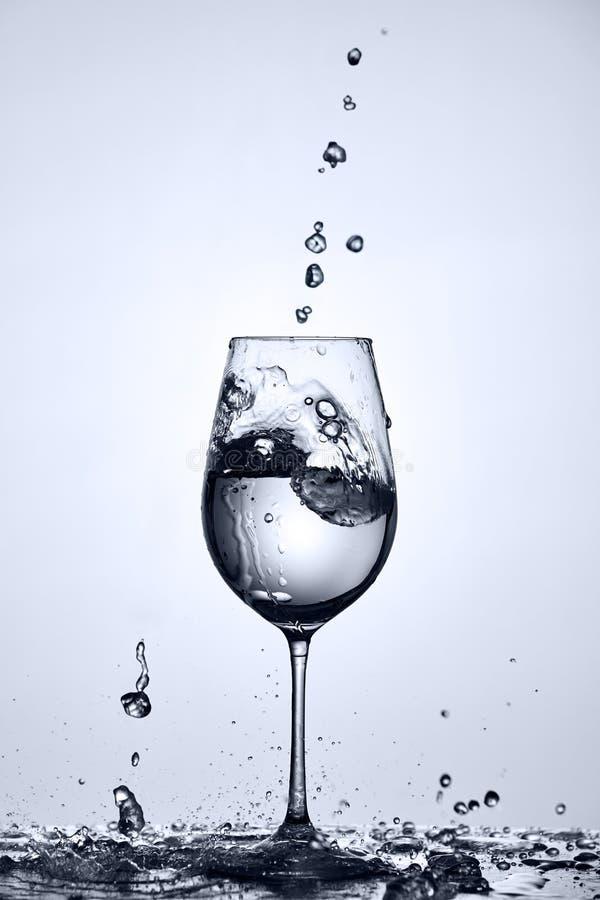 Wasserblasen, die fallen und Trinkwasserspritzen aus dem Weinglas heraus, das auf dem Glas gegen hellen Hintergrund steht stockfotografie