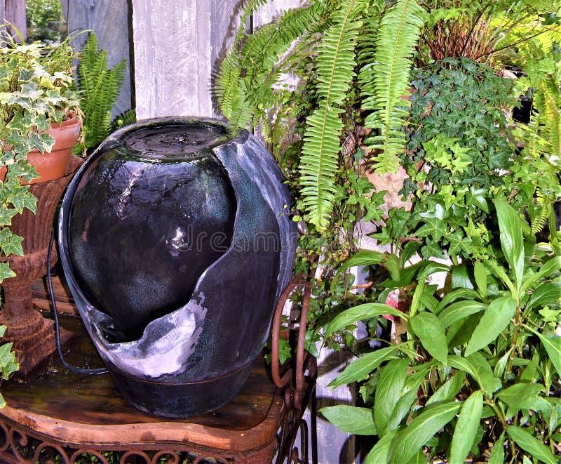 Wasserbrunnen des dekorativen Steins angeschmiegt unter Grün lizenzfreies stockbild
