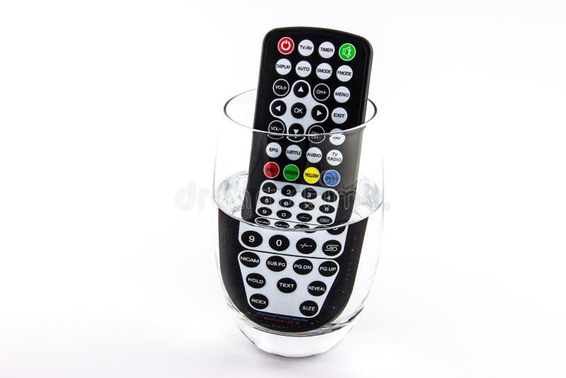 Wasserdichte Fernsehfernbedienung in einem Glas Wasser lizenzfreies stockfoto