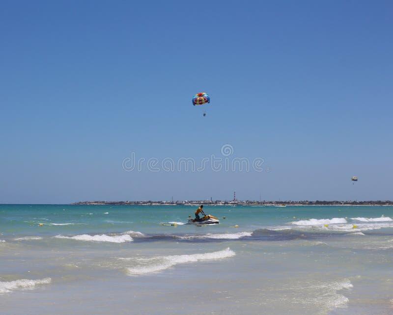 Wasserfahrrad mit einem Mann im Meer Wasserfallschirme fliegen in den Himmel oben stockfoto