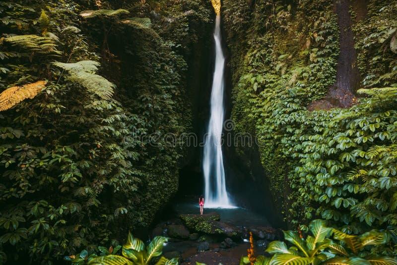 Wasserfall im tropischen Dschungel und allein Frau in Bikini Leke Leke Wasserfall in Bali lizenzfreies stockfoto