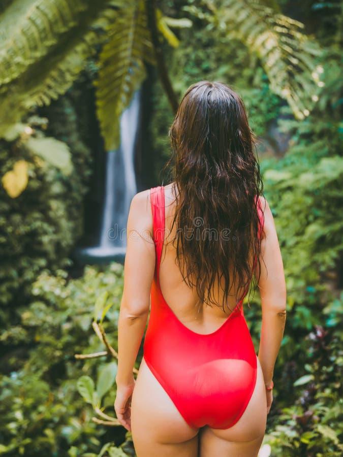 Wasserfall im tropischen Dschungel und allein Frau in Bikini Leke Leke Wasserfall in Bali stockbilder