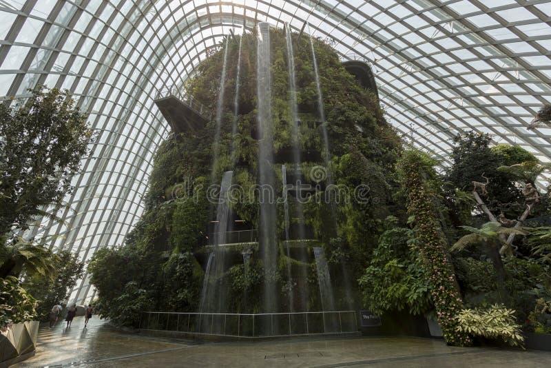 Wasserfall innerhalb der Wolke Forest Dome Gardens durch die Bucht in Singapur Auf Hintergrund einige Touristen, die vorbei gehen stockfotografie