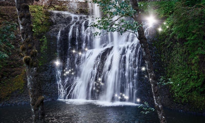 Wasserfall mit feenhaften Lichtern des Tanzens in verzaubertem Wald lizenzfreie stockfotos