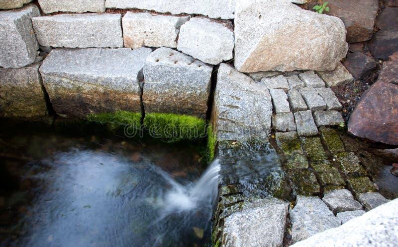 Wasserfall neben großen Steinen lizenzfreie stockbilder