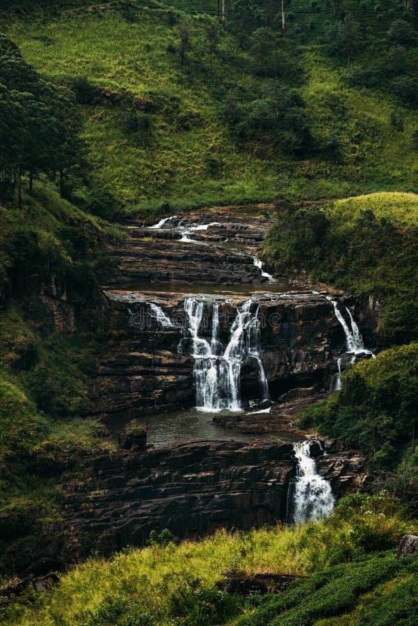 Wasserfall unter den grünen Bergen Wasserfälle in Sri Lanka Landschaften Asiens Luftaufnahmen Teeplantage Grüner Hügel lizenzfreies stockbild