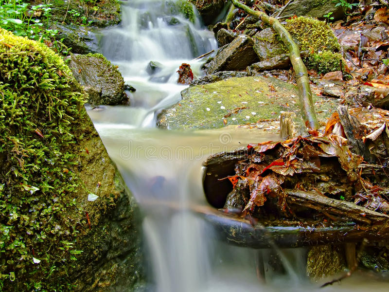 Wasserfallnahaufnahme unter Felsen und Moos lizenzfreies stockbild