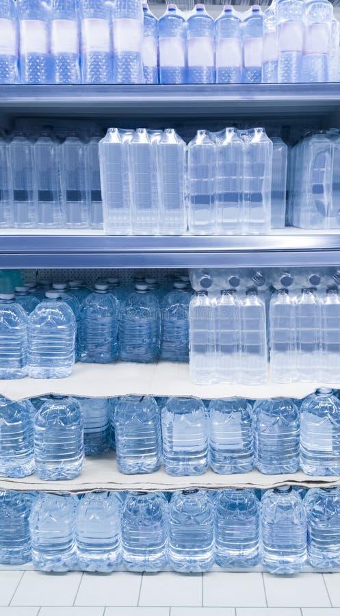 Wasserflaschen auf Regal lizenzfreie stockbilder