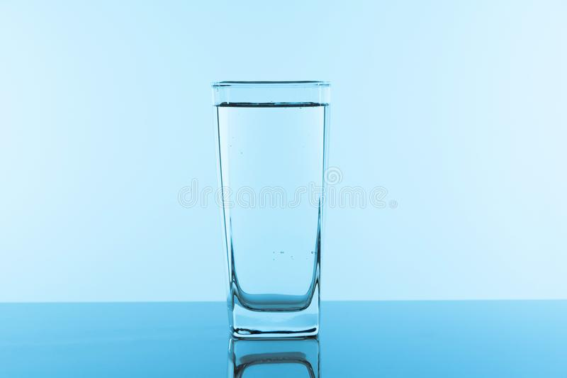 Wasserglas auf blauem Hintergrund Glas mit sauberem Trinkwasser stockbilder