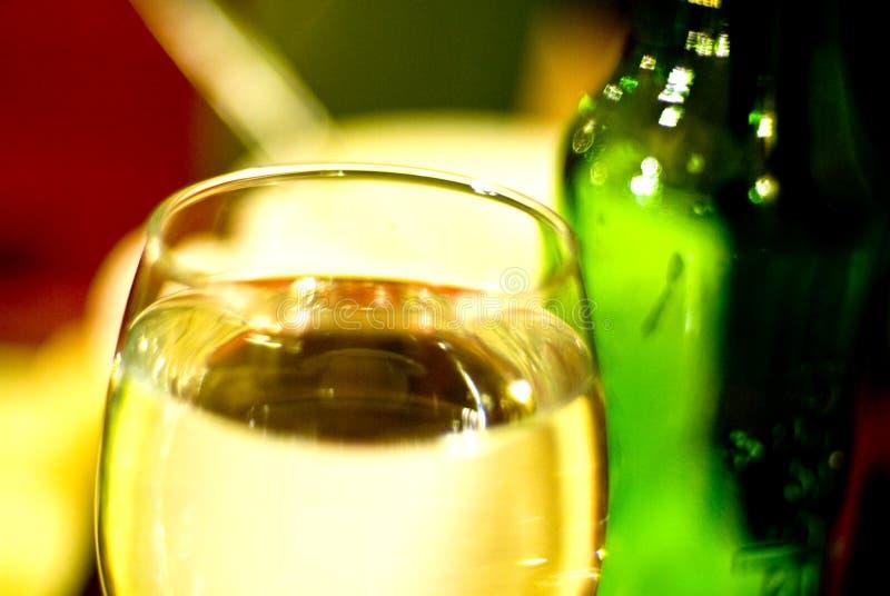 Wasserglas und grüne Flasche lizenzfreie stockfotos