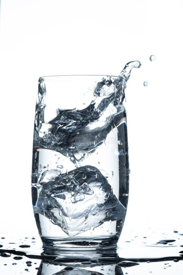 Wasserglaseiswürfelspritzen im vertikalen Format lizenzfreie stockfotografie