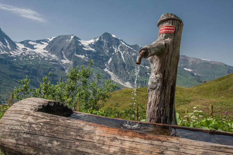 Wasserhahn in einem hölzernen Stumpf in Grossglockner Österreich lizenzfreie stockbilder