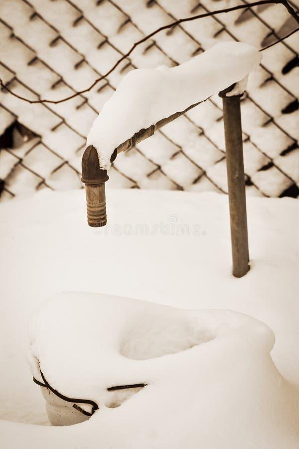 Wasserhahn im Garten unter Schnee, Sepia stockbild