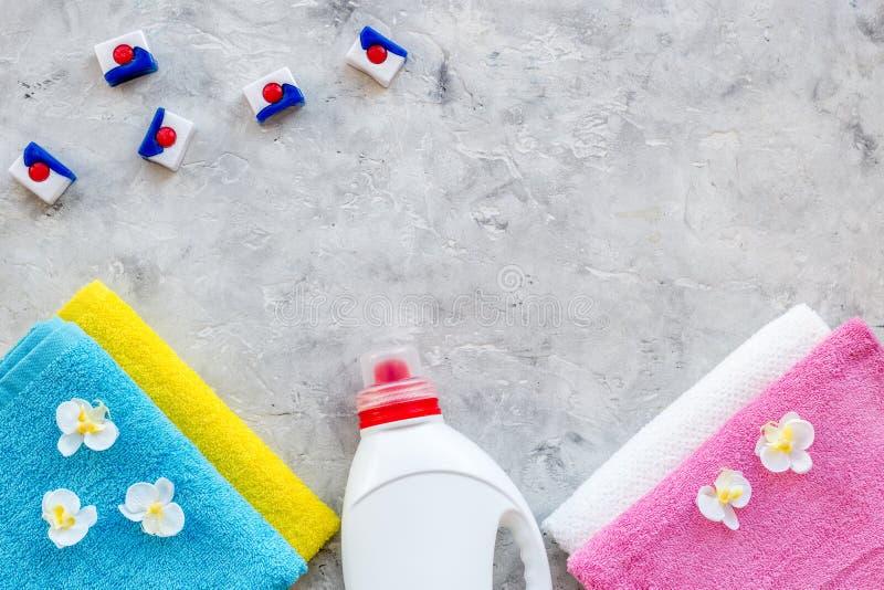 wasserij Droog en vloeibare detergentia dichtbij schone handdoek op grijze steen hoogste mening als achtergrond copyspace stock foto