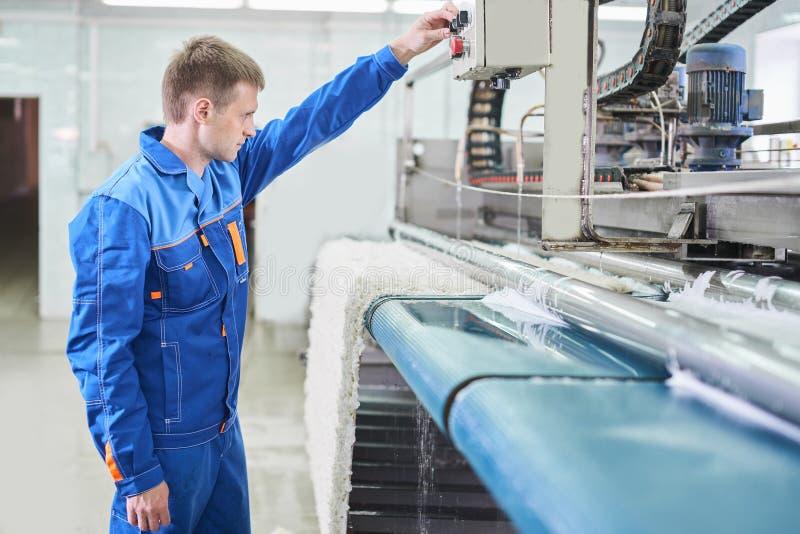 Wasserijarbeider tijdens het werken aan automatische machine voor tapijtwas royalty-vrije stock foto