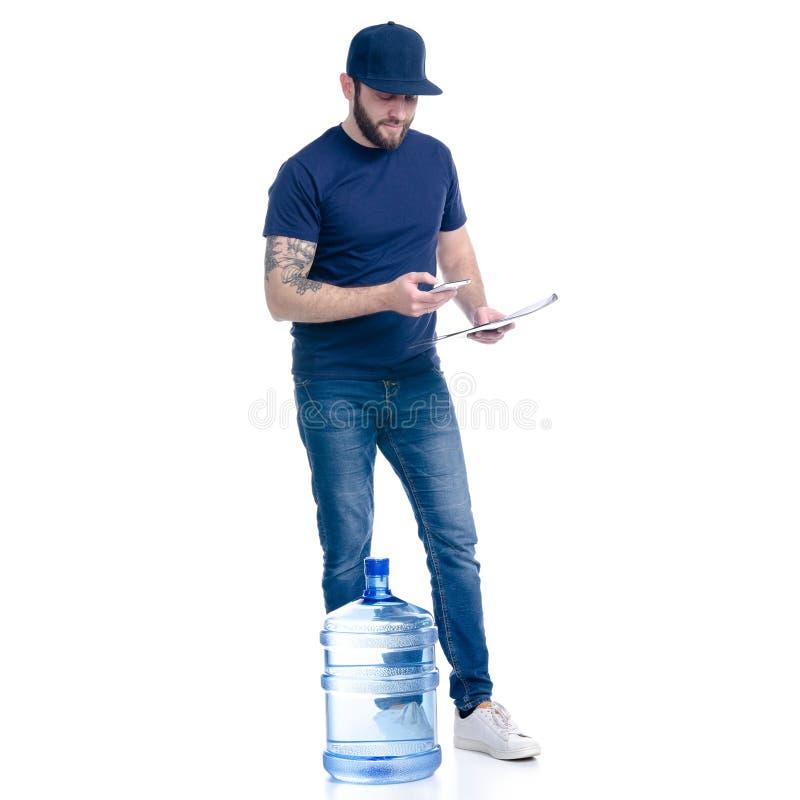 Wasserlieferer im blauen T-Shirt und in der Kappe mit Smartphone- und Dokumentenrechnungsunterzeichnung lizenzfreie stockfotografie