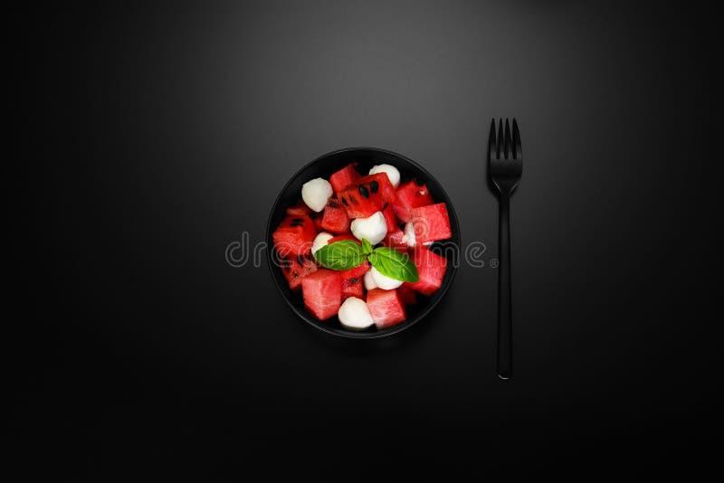 Wassermelone in der schwarzen Schüssel stockbilder