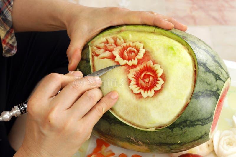 Wassermelone-Erscheinenjobstep der Frau Hände geschnitzter stockfotos