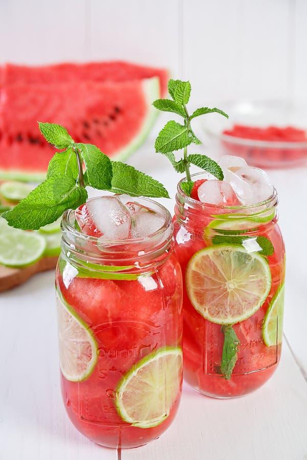Wassermelone, Kalk und Minze hineingegossenes Wasser lizenzfreie stockbilder