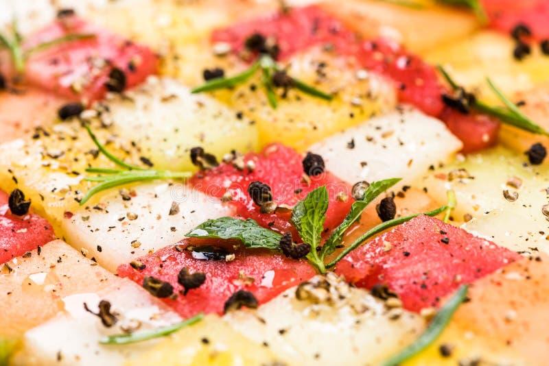 Wassermelonen-und Melonen-Würfel mit Kräutern und Gewürzen, Draufsicht, kreative Partei-Nahrungsmittelumhüllung stockfotografie